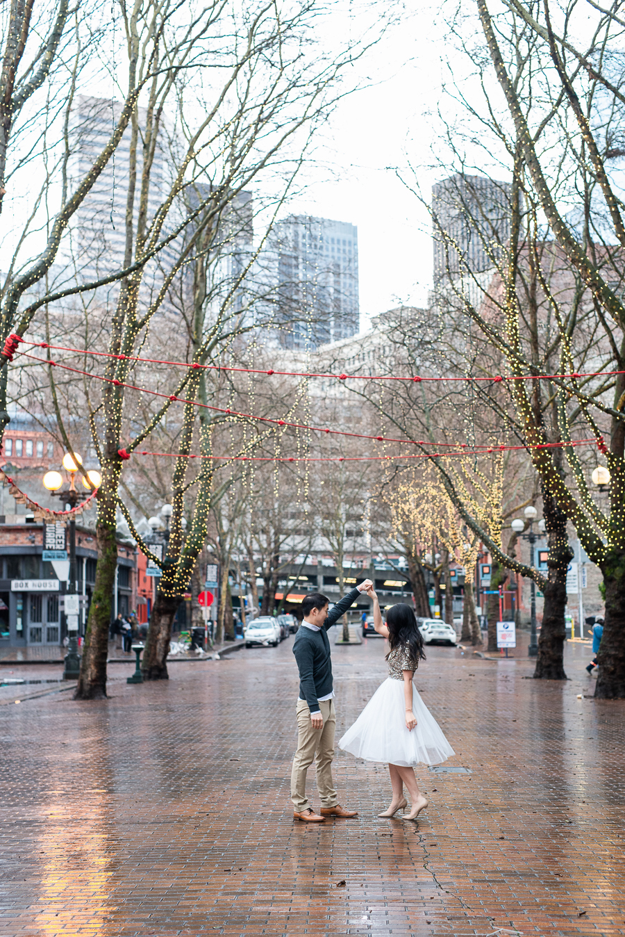 Seattle Engagement Photos In Pioneer Square Occidental Park Holiday Shoot Rainy Engagement Photos With Clear Umbrella Seattle Fashion Blogger Just A Tina Bit Midi Tulle Skirt Embellished Top Sequined Top Just