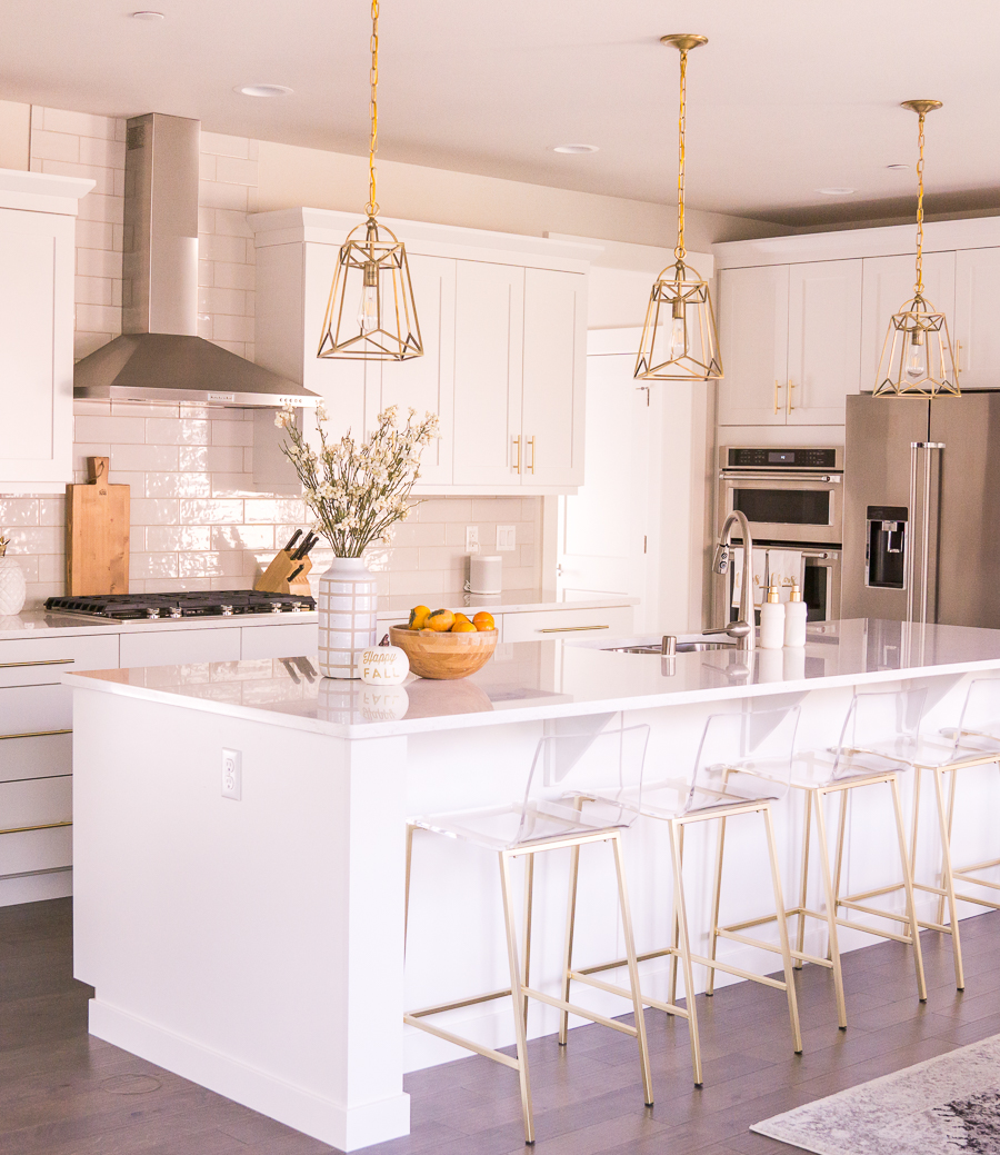 White Kitchen With Brass Pendant Lights, Clear Acrylic Bar Stools, White  Countertops, Kitchen Inspiration, Home Decor Blogger